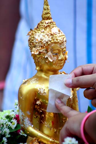Applying gold leaf to a Buddhist statue is a way to make merit in Thailand. It's also a good way for a temple to make some bucks.